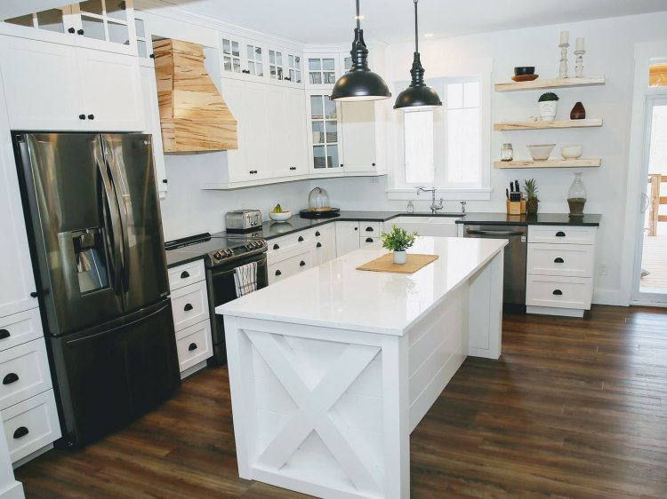 Black pendant lights over a custom island in a white kitchen with black and natural wood accents