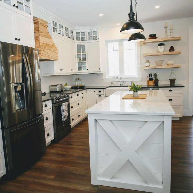 Kitchen with white fittings, custom island, and black appliances and accents